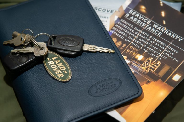 Log book of a vehcile with a key on top. There is also a Landrover badge on the keychain