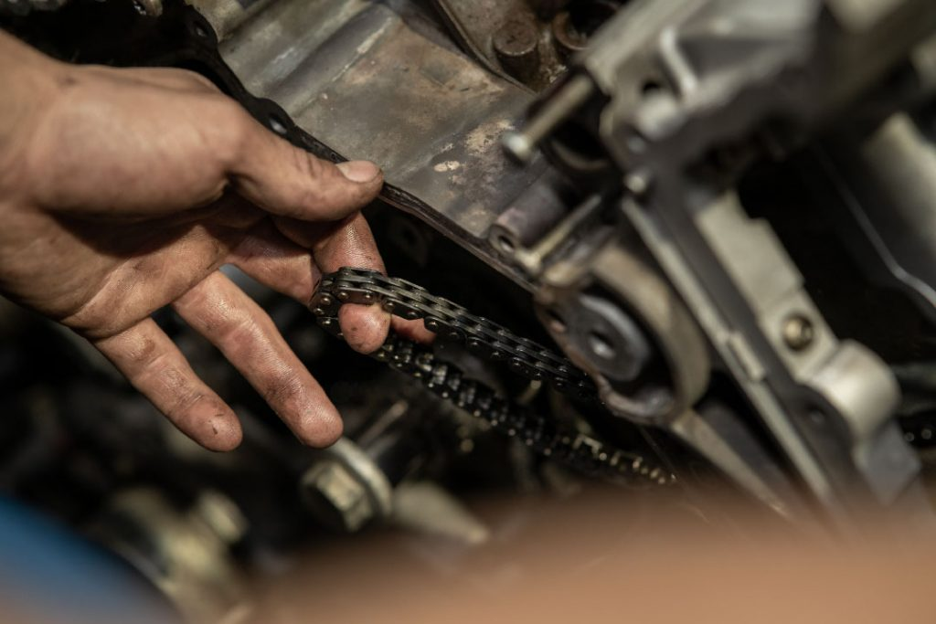 Person working on a vehicle, pulling at a chain that is attached to an engine. Can only see their hand